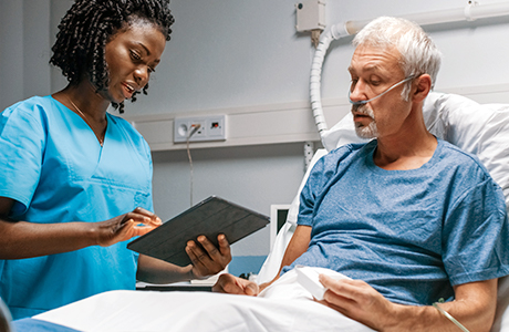 Doctor stands at patient's bedside with digital patient documents