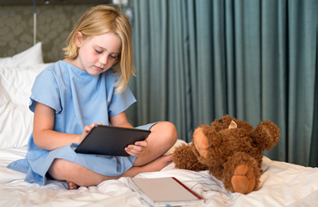 Little girl watches movie on tablet with her teddy in hospital bed