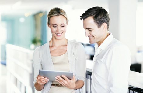 Two people in the office at a tablet